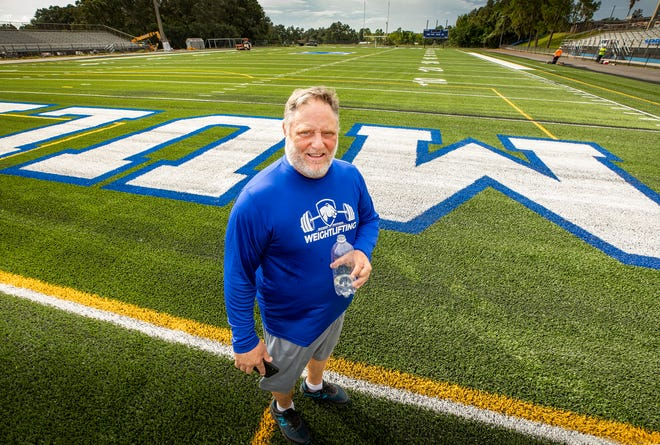 Mulberry High School football coach Kevin Wells walks across the new artificial turf that has been installed at Mulberry High School.
