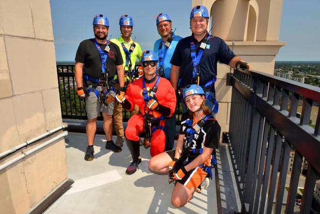 Chris Mellone from Essex Hotel Management; Mark Swinnerton, Jordan Witte, Jerry Mosier and Geoff Cook from TAYLOR – The Builders; and Pace Electronics-sponsored Scout Lilyan Short, of Webster's Troop 425, accept the challenge to rappel 21 stories down Kodak Tower in downtown Rochester to support the Seneca Waterways Council's Urban Scouting program.