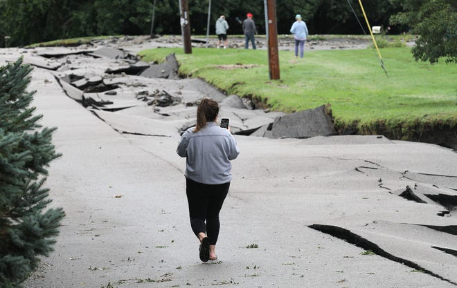 A woman takes video of the destroyed roadway along Fairview Lane in Portsmouth on Thursday morning.