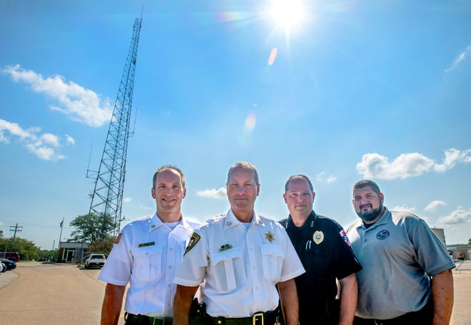 From left to right: Pekin Deputy Fire Chief Tony Rendleman, Tazewell Co. Sheriff Joe Lower, Pekin Police Chief John Dossey, and ETSB 911 coordinator Mike McIntyre pose near the big communications tower at the Tazewell County Consolidated Communications center on Koch Street in Pekin. City and county law enforcement and emergency services are transitioning to a new state-of-the-art Starcom21 radio system that will vastly improve communications.