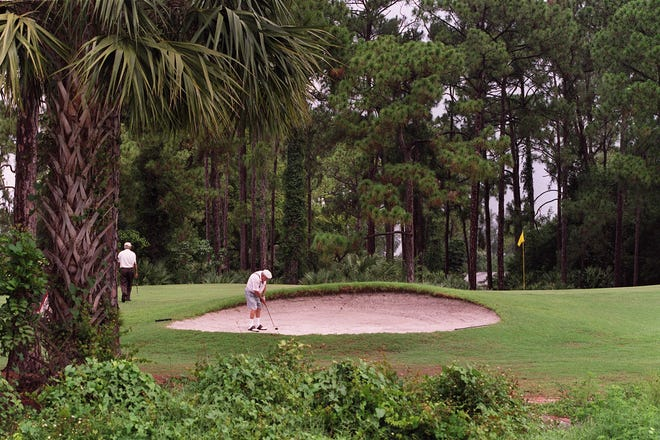 In this June 2001 photo, a golfer at the Forest Oaks golf course at Lucerne Lakes in Lake Worth Beach plays out of a sand trap. The course is set to become a housing development.