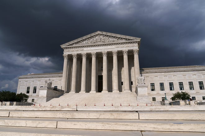 In this June 8, 2021 photo, with dark clouds overhead, the Supreme Court is seen in Washington.