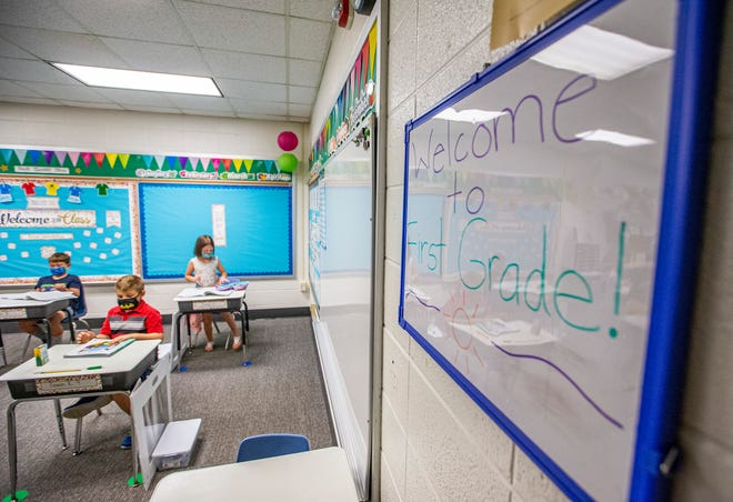 Kids in a first grade classroom at Hums Elementary School wear masks and sit at desks that are spread out on Thursday, Sept. 2, 2021, in Mishawaka.