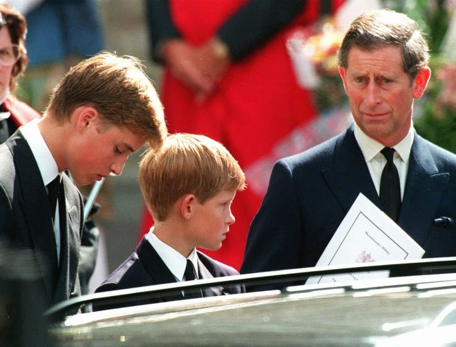 In this Sept. 6, 1997, photo, Prince Charles, the former husband of Diana, Princess of Wales, and their two sons Harry, center, and William wait in front of Westminster Abbey in London after the funeral ceremony of the princess.