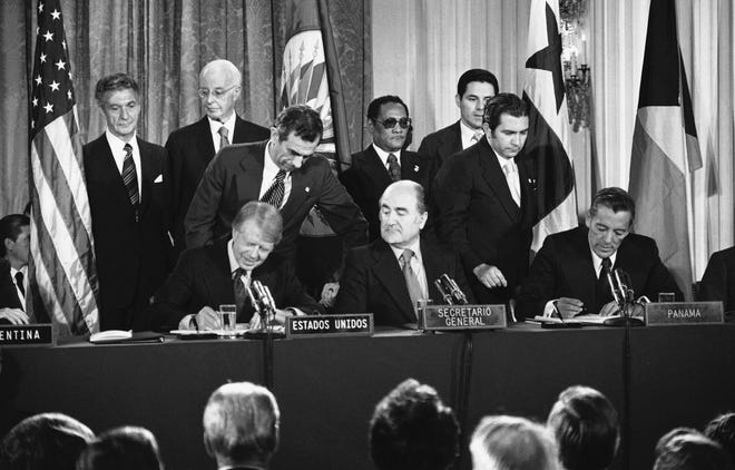 Officials execute the Panama Canal treaty on Sept. 7, 1977, at the Pan American Union in Washington. Seated from left are President Jimmy Carter, Organization of American States Secretary General Alejandro Orfila and Panama's head of government Omar Torrijos.