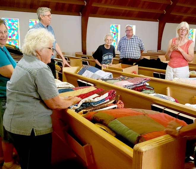 Elizabeth Bower, Barbara Frisbie,Pastor David Reed of Orphan Grain Train-Michigan,Connie Addis, St. Paul's Lutheran Pastor Kurt Kuhlman and Jeanne Lee, at a prayer of dedication of quilts and winter clothes.