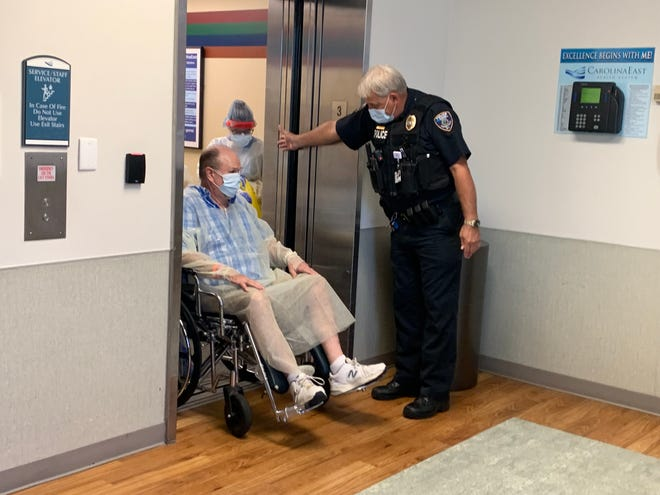 Lt. Alvin Hoell helping a patient out of the elevator at CarolinaEast hospital. He is one of the 20 officers that work at the hospital.