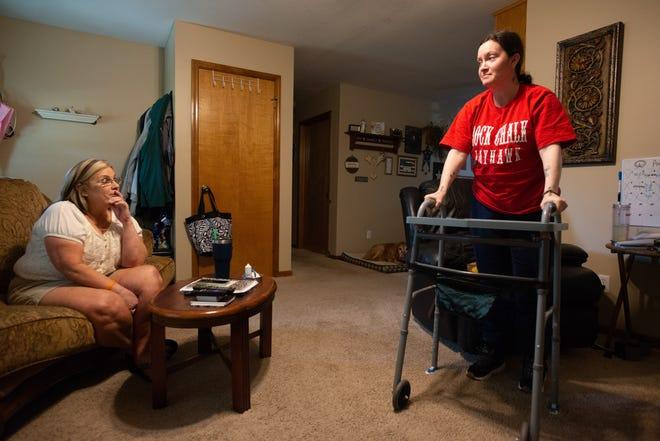 Erika Hundley stands with the help of a walker after talking about her battle with Guillain-Barre syndrome, which was triggered by her COVID-19 diagnosis in May 2020. Her mother, Kellie Hundley,  of Holton, has been instrumental in her recovery.