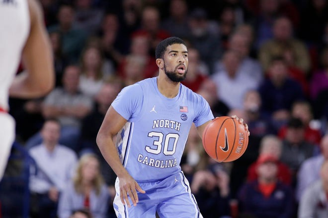 North Carolina guard K.J. Smith (30) brings the ball up the court during the second half of an NCAA college basketball game against Gonzaga in Spokane, Wash., on Wednesday, Dec. 18, 2019. After appearing in 51 games over three seasons for UNC as a reserve point guard, Smith graduated in 2021 and now works as a national basketball analyst for On.3.com, a startup website covering college sports and recruiting.