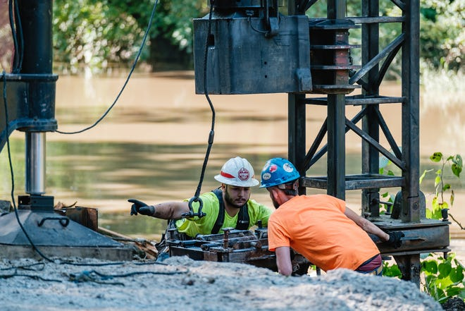 Crews from the Tuscarawas County Engineer's Office work to drive pilings in between the banks of Big Stillwater Creek and Waterworks Hill Rd SE, Thursday, September 2 in Mill Township. The road began to crumble after a dam was removed on the creek. Pictured, is Carter White, left, from Uhrichsville, and Levi Kaser, guiding part of the pile driver rig into position. The rig was being operated by Matt Cappillo, not pictured.
