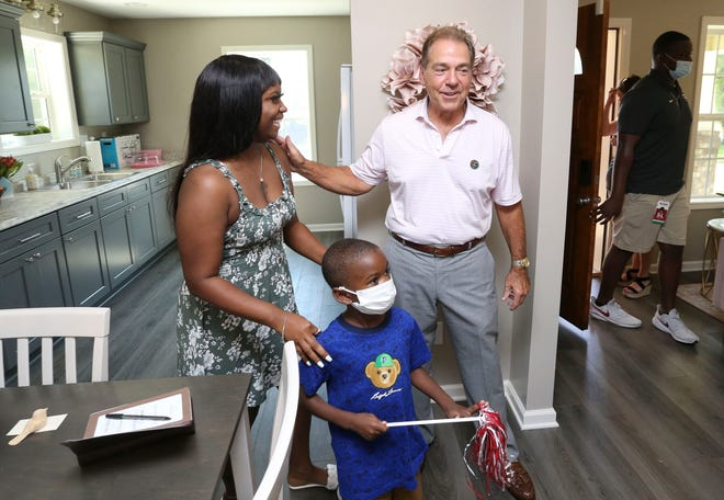Habitat for Humanity of Tuscaloosa in partnership with the Nick's Kids Foundation dedicated the 18th house built by the foundation in commemoration of the University of Alabama's 18th National Championship Thursday, Sept. 2, 2021. Nick Saban congratulates new homeowner Joselyn Hamner and her son, Jayceon Loggins in the dining area of their new home. [Staff Photo/Gary Cosby Jr.]