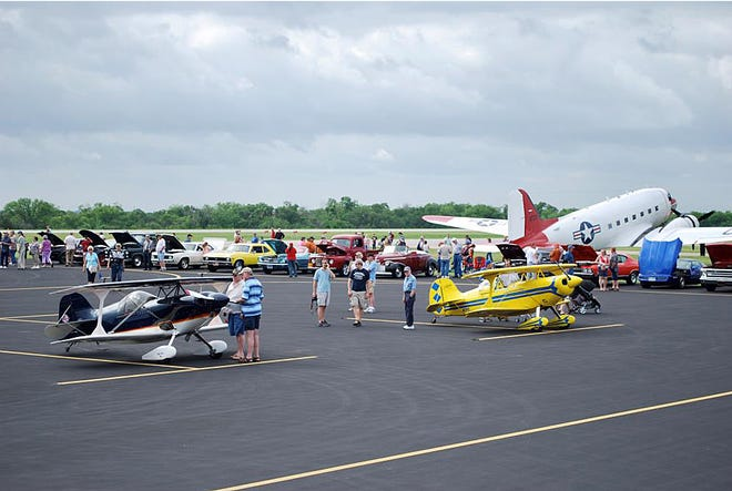Enthusiasts get a look at vintage airplanes and classic cars during a previous Wings-N-Wheels event at Mid-Way Regional Airport. The airport will hold its annual fly-in, drive-in event on Saturday, Sept. 18.