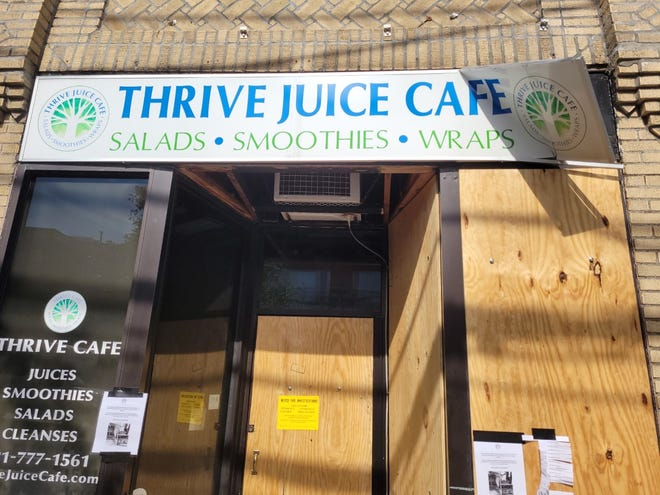 The boarded up front of Thrive Juice Cafe after the fire on Aug. 25.