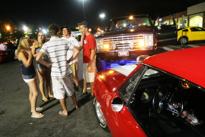 Drivers stand in front their cars after cruising Patton Avenue on Friday night, June 13, 2007.
