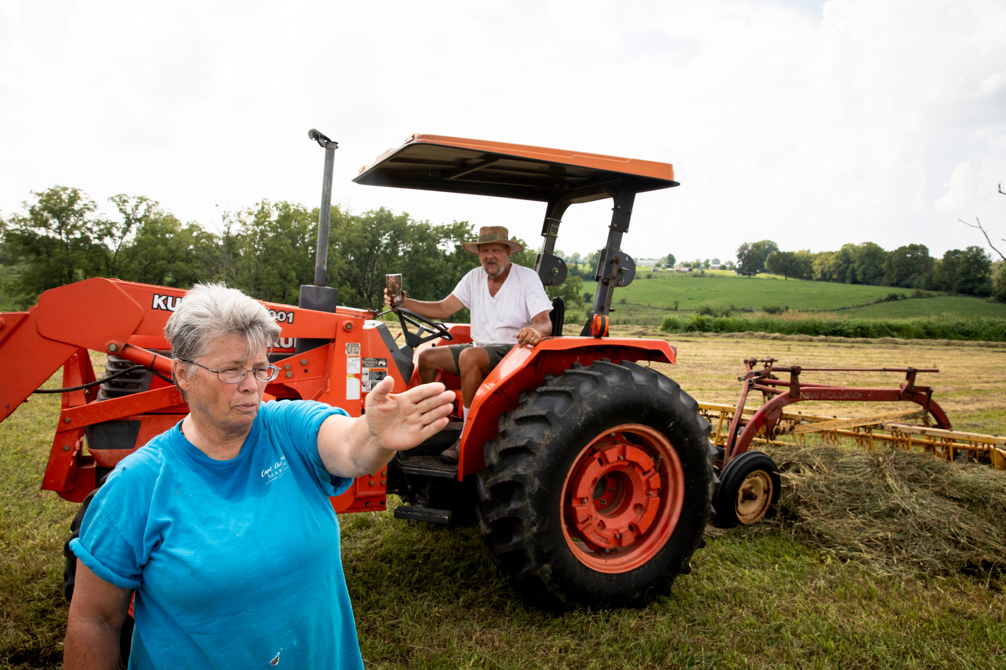 Pam McCauley talks with her husband while he breaks from mowing their field in Harrison County, Ky., on Wednesday, August 25, 2021.