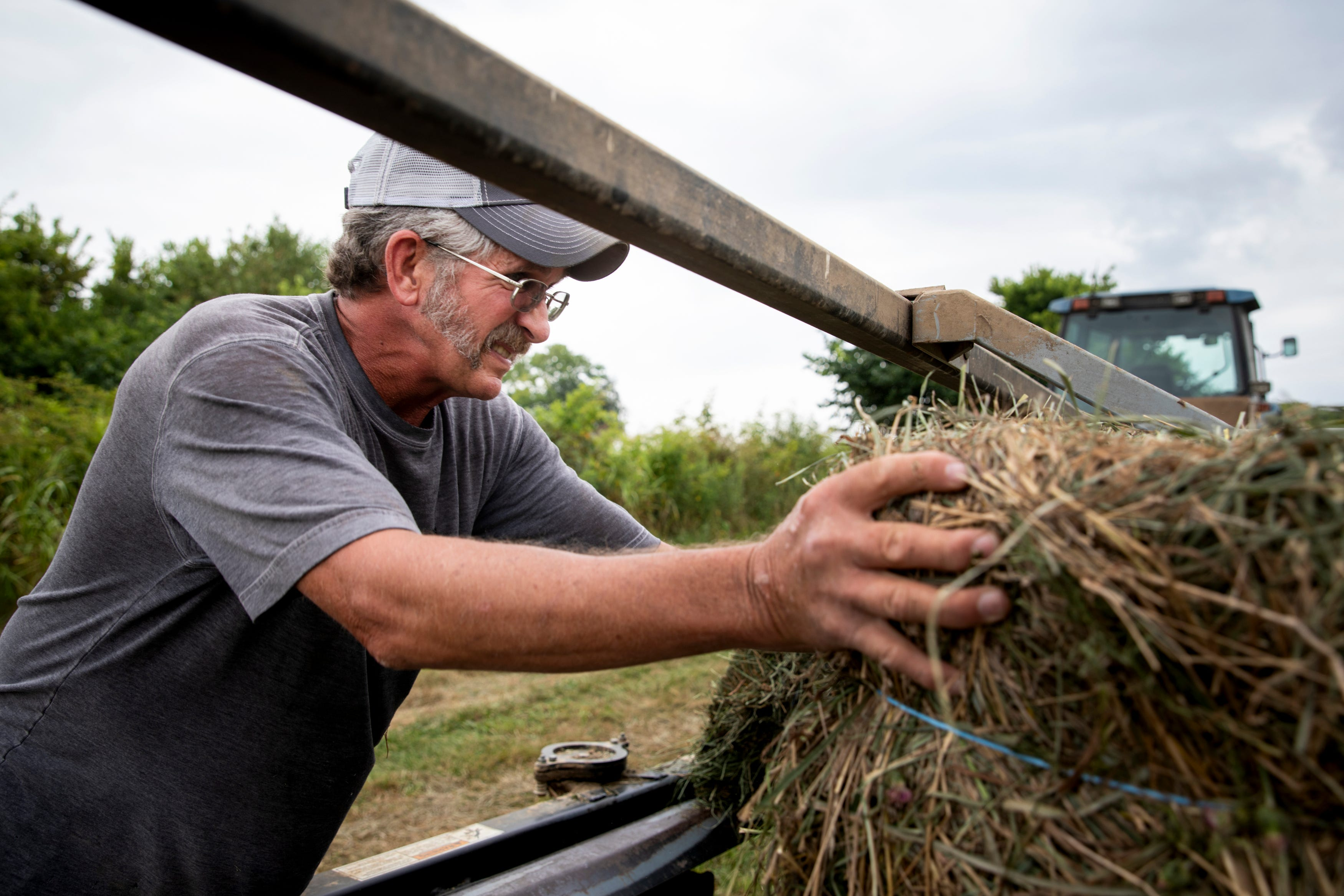 Troy Bradford works on his hay baler on his farm in Harrison County, Ky., on Monday, August 9, 2021.