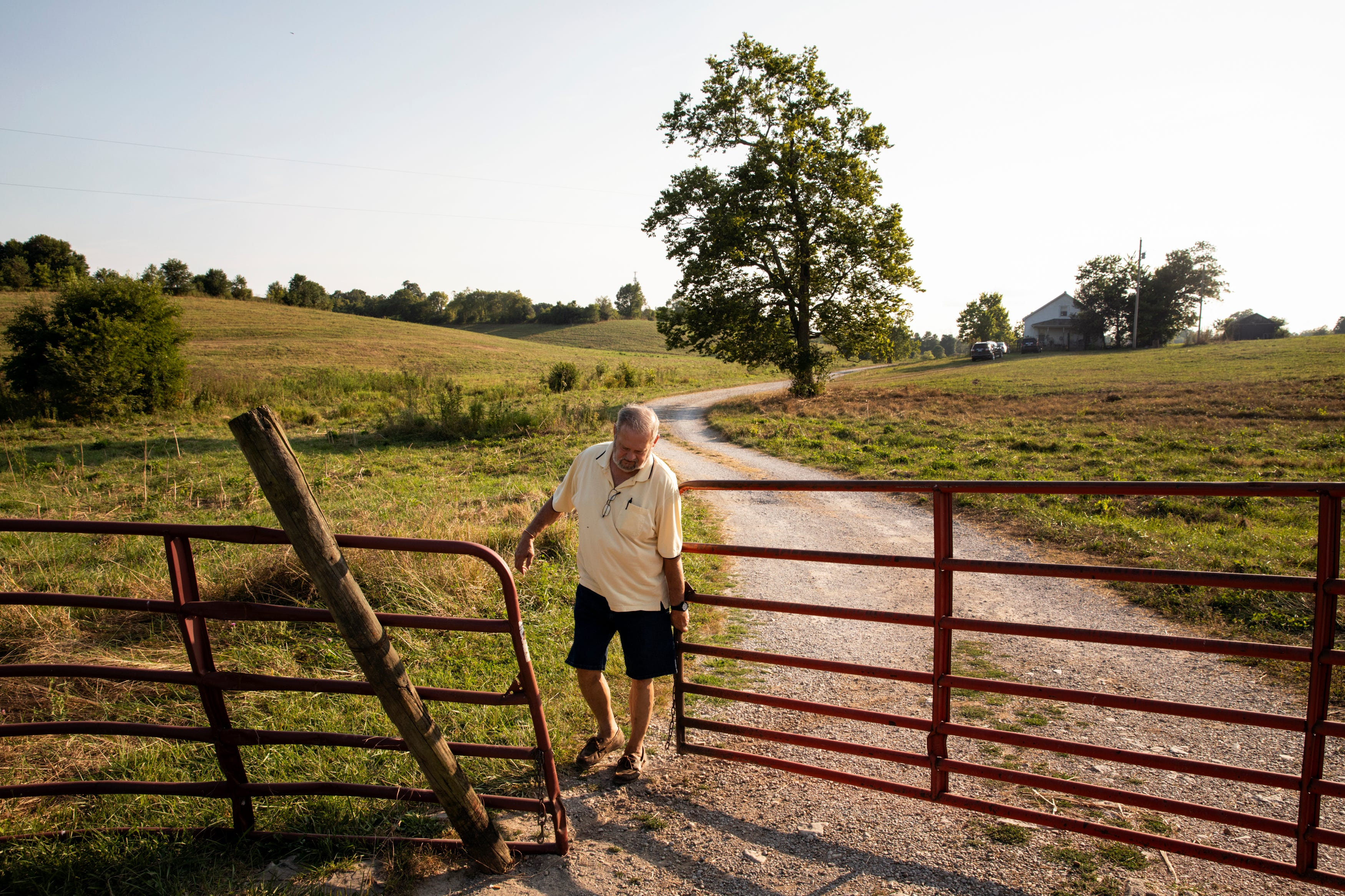 Skip Kuster closes the gate to his farm in Harrison County, Ky., on Sunday, August 8, 2021.
