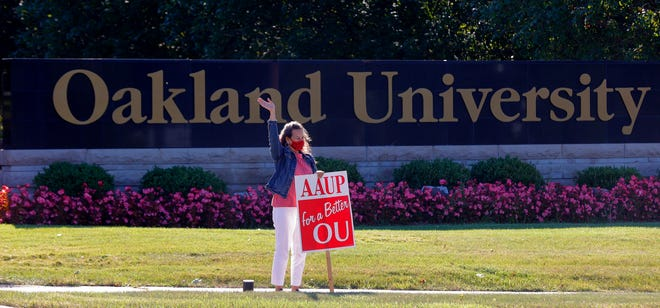 Annette Feravich, 56 of Commerce Township, waves at passing cars honking their support for her and other professors at Oakland University in Rochester on September 2, 2021. From tenured to special lecturers they stood out in shifts to call attention to the union's contract that expired on Wednesday night. The professors want better pay and benefits.