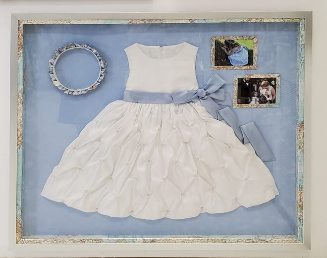 Master Certified Picture Framer Janine Buechner, owner of Blue Moon Framery in Sturgeon Bay, specializes in museum-level preservation. One example is this shadow box display of a flower girl dress for a map-themed wedding.