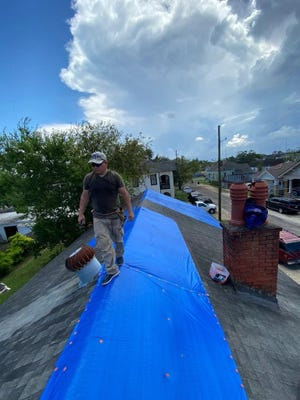 Volunteers from the Krewe of Red Beans install tarps on a roof in New Orleans in the days after Hurricane Ida.