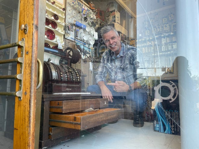 Jerry Millen stands in a front window of the former Rolison PRO Hardware building in Brighton, which he purchased. Millen also had the winning bid on an antique cash register at the store, shown Thursday, Sept. 2, 2021.
