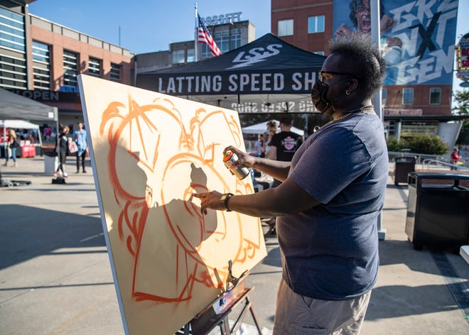Local artist Quantavious Worship sprays paint onto a canvas during the 901 Day Exposure event at the FedExForum courtyard on Wednesday, Sept. 1, 2021.