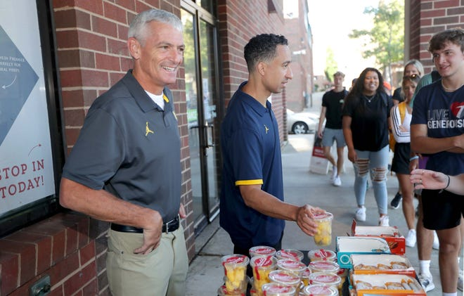 Marquette University President Michael Lovell, left, is joined by men's basketball coach Shaka Smart in handing out granola bars and fruit cups to students at the Sendik's Fresh2GO on the Marquette campus on the first day of classes Monday. Lovell announced Wednesday that he has a rare form of cancer.