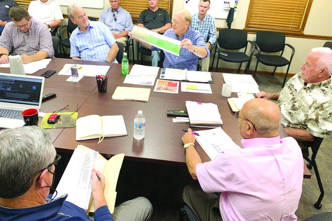 Concerned citizens, transportation executives, business leaders, and local government representatives from the areas of Boone, Marion, and Baxter counties of Arkansas met at the Harrison Chamber of Commerce Thursday afternoon to discuss the Highway 412 highway system. Richard Sheid from Mountain Home holds up a map of the Highway 412 road system that runs through the northern part of the state of Arkansas that travels east and west from Oklahoma and Tennessee.