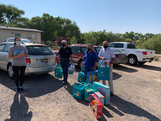 From left to right, Childhaven Foundation Development Director Andrea Pena, is surprised by PNM director of the San Juan Generating Station Rodney Warner, PNM employee Mickey Marquez and PNM retiree Joe Gonzales with donations on Aug. 31 at the Childhaven administration building in Farmington.