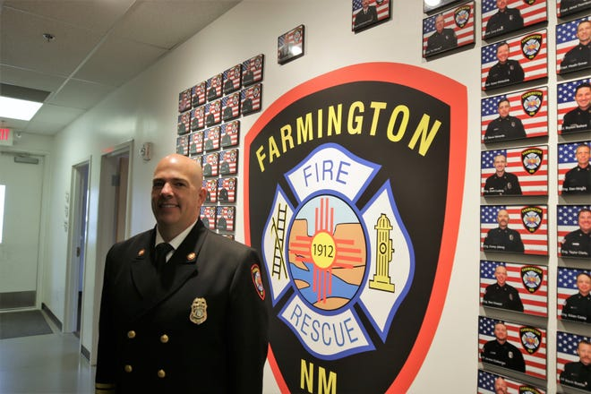 Farmington Fire Chief Robert Sterrett poses in front of a display in the Farmington Fire Department administration building at 301 N. Auburn Ave.