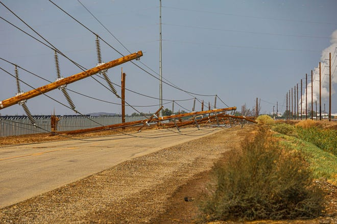 Power poles rest along a road in Imperial County after a storm Tuesday night downed more than 100 power poles in IID's major transmission corridors between Calipatria and Niland.