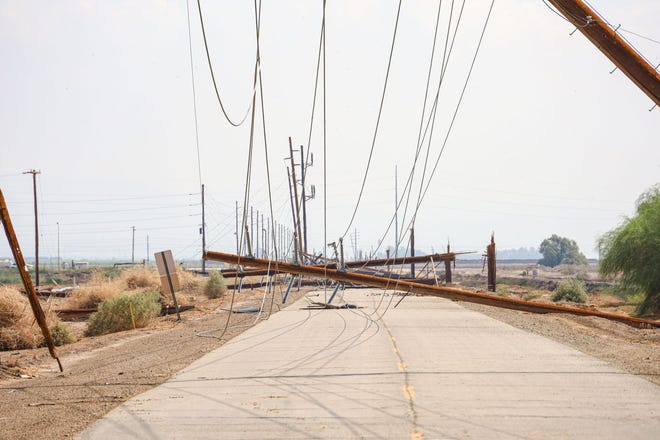 Power polls rest along an Imperial County road following a storm Tuesday night that downed more than 100 IID power polls.