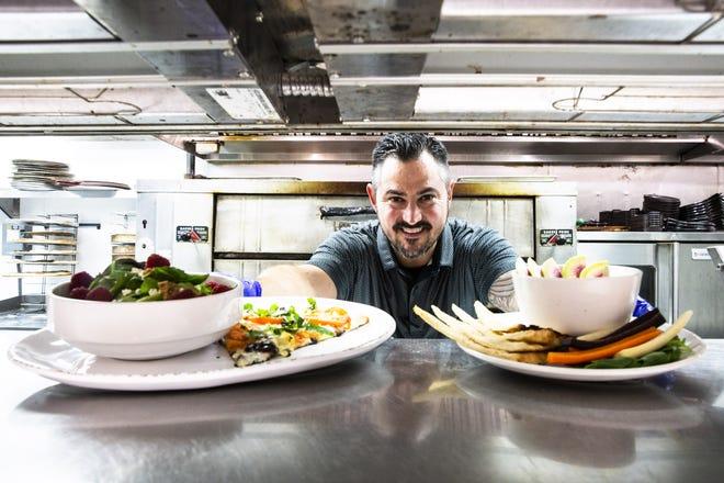 Il proprietario Chris Disney serve del cibo dalla cucina della Healthy Italian Kitchen di Picasso il 1° settembre 2021 a Gilbert, Aris.