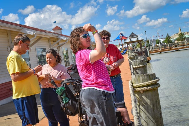 Program Coordinator Janessa Lopez, second from left, distributes containers of fish food so clients can feed the fish in the pond outside The Landing. The Landing in Port Clinton is Wynn-Reeth's newest Adult Day Support site.