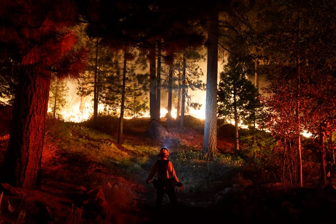 A firefighter monitors the Caldor Fire burning near homes in South Lake Tahoe, Calif., on Monday, Aug. 30, two weeks after the fire started. Full containment is expected Monday, Sept. 27.