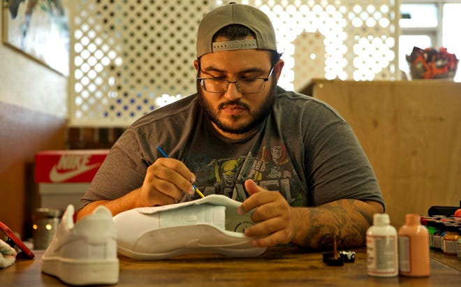 Lou Pabon paints a design on a pair of shoes in his new shop on Sherwood Way on Wednesday, Sept. 1, 2021.