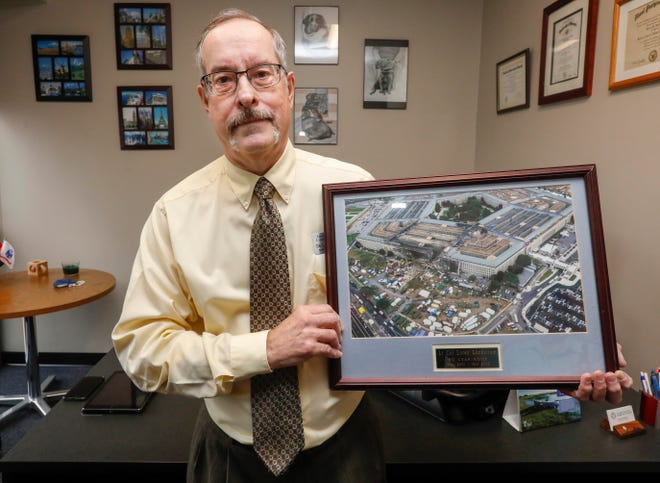 Dr. Loren Lundstrom, dean of student development at OTC, holds a picture of the Pentagon after the attack on Sep. 11, 2001.