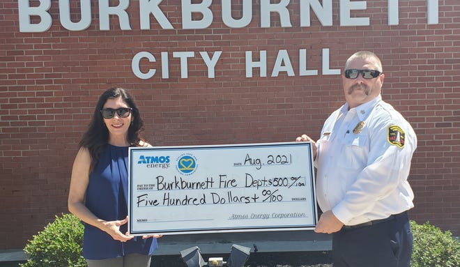 Pam Hughes Pak with Atmos Energy presents a check to Harold Watkins, Burkburnett Fire Chief, for $500.