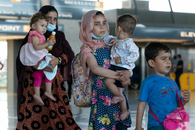 Families evacuated from Kabul, Afghanistan, walk through the terminal before boarding a bus after they arrived at Washington Dulles International Airport, in Chantilly, Va., on Thursday, Sept. 2, 2021.