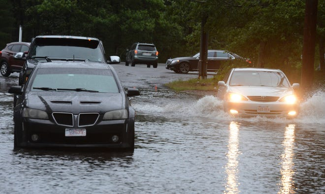Vehicles drive through a flooded street from the remnants of Hurricane Ida on Thursday, Sept. 2, 2021 in Yarmouthport, Massachusetts.