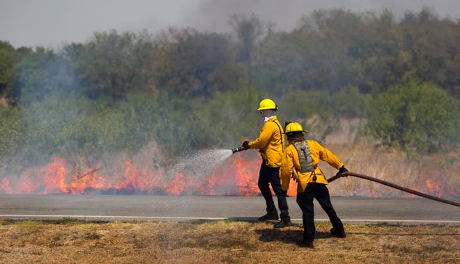 Firefighters battle a grass fire on Cele Road in Pflugerville on Sept. 4, 2011.
