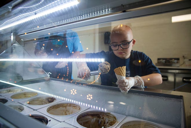 Tyler Candido, 10, scoops ice cream at Udder Love in Liberty Hill. His parents, Lisa and James Candido, opened the shop in August to give their son, who has Down's syndrome, a chance to get some work experience.