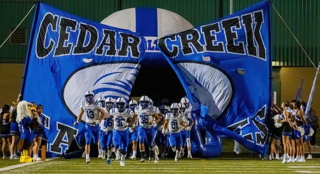 Cedar Creek football players enter the field to begin the second half during the Eagles' game versus Akins on Sept. 2