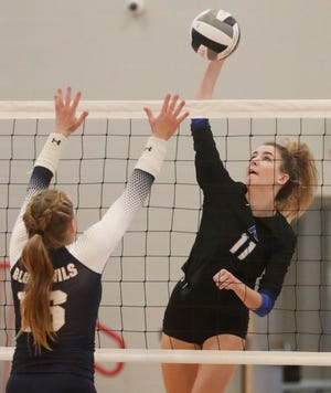 Revere's Presley Baker hits the ball as Tallmadge's Ella Bee defends during the Minutemen's volleyball victory Thursday night. [Mike Cardew/Beacon Journal]