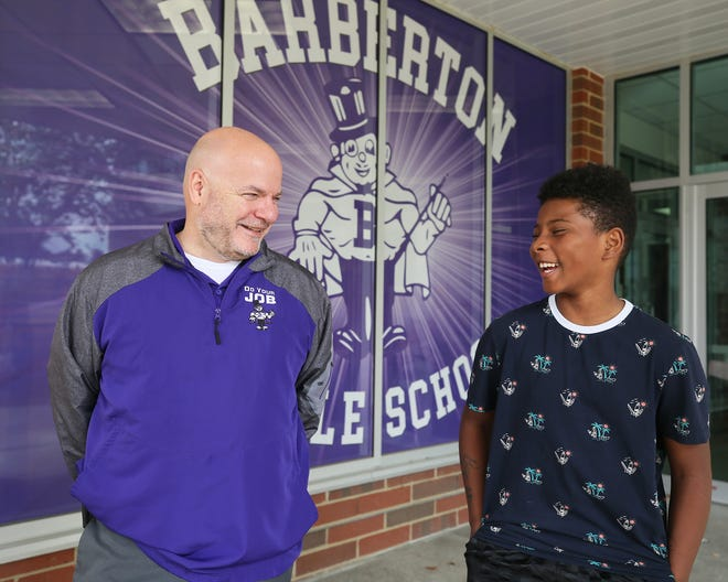 Anthony Hermann, eighth grade assistant principal, and J'Marion Rogers, 13, share a smile as they talk Friday about their experience at Barberton Middle School.
