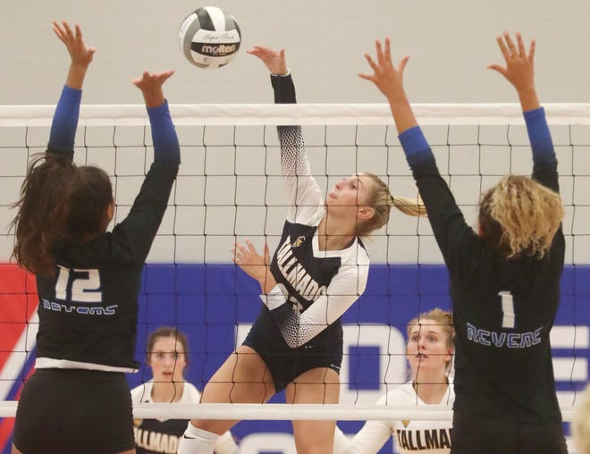 Tallmadge Mia Hurst, center, hits between Revere defenders Jessa Randall and Jackie Randall during the volleyball match at Revere High School on Thursday, Sept. 2, 2021, in Richfield.   [Mike Cardew/Akron Beacon Journal]