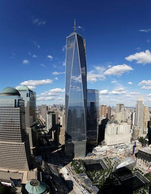 One World Trade Center towers over the wedge-shaped pavilion entrance of the National September 11 Museum, lower right, and the square outlines of the memorial waterfalls in New York. The marquee skyscraper at ground zero, One World Trade Center rises from the northwest corner of the site.