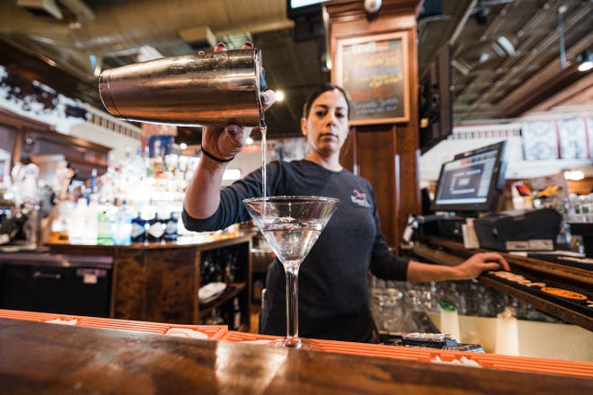 Bartender Lisa Macias pours a drink for a customer at the Painted Horse on Friday.