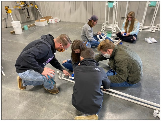 Bartlesville FFA members build sanitizing stations during agriculture education class. The stations were funded by a  Living to Serve grant from the national FFA organization.