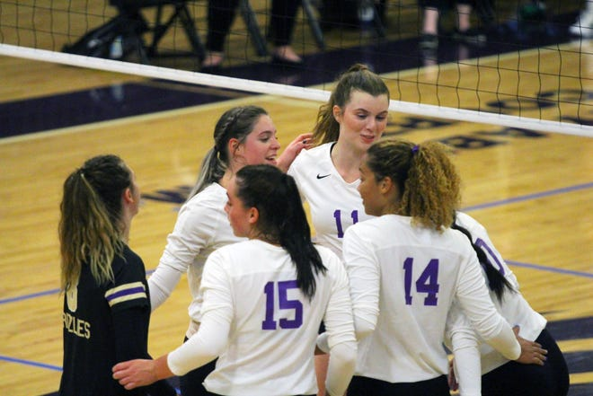 The Butler Grizzlies volleyball team huddle after winning a point against Colby on Wednesday, Sept. 1 at the Power Plant in El Dorado, Kansas.
